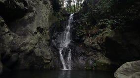 Woman exploring waterfall in tropical jungle. Tourist girl enjoying and watching mountain stream falling through dark rocks. Ten (10) meters high waterfall stock video