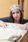 Woman expresses concern about her preparation of handmade pasta Royalty Free Stock Photography