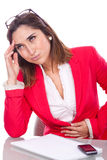 Woman with expression of pain and discomfort at work Stock Image