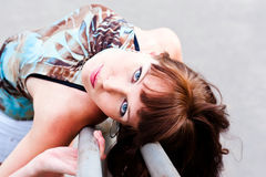 Woman with expressive eyes. Beautiful woman lays back on the rails Royalty Free Stock Photography