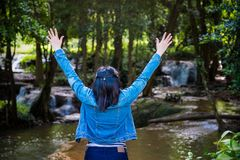 The woman is extending the arm from the body for a show glad and happy to arrive. In there stand on the stream from the waterfall stock photography