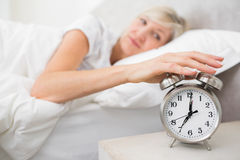 Woman extending hand to alarm clock in bed Royalty Free Stock Photography