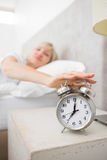 Woman extending hand to alarm clock in bed Royalty Free Stock Photos