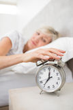 Woman extending hand to alarm clock in bed Stock Photos