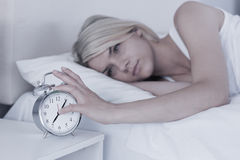 Woman extending hand to alarm clock in bed Royalty Free Stock Images