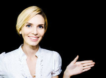 Woman extending her hand in endorsement. Stylish beautiful blonde woman extending her hand and pointing in an endorsement of your product or advertisement as she Stock Photo