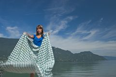Woman extending a tablecloth Royalty Free Stock Photography