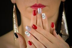 THE WOMAN HAS RED,black,glittering silver and white nails with heart.She holds her palms in front of her face. She has red lips. Woman with extravagant earrings stock photos