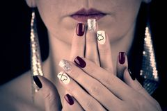 THE WOMAN HAS RED,black,glittering silver and white nails with heart.She holds her palms in front of her face. She has red lips. Woman with extravagant earrings royalty free stock photography
