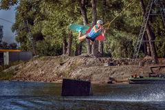 Woman extreme sports on a wakeboard. Woman extreme sports on a wakeboard to jump up Royalty Free Stock Photography