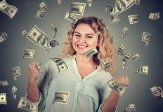 Woman exults pumping fists celebrates success under money rain Royalty Free Stock Image