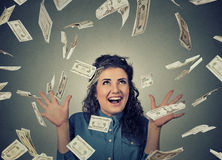 Woman exults pumping fists ecstatic celebrates success under money rain falling down dollar bills banknotes Royalty Free Stock Images