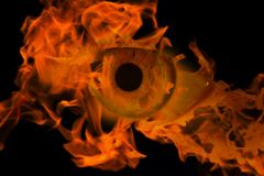 Woman eye with burning fire in it royalty free stock photos
