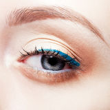 Woman eye. Closeup shot of woman eye with day makeup and blue arrow Royalty Free Stock Image