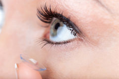 Woman eye with contact lens applying Stock Photo