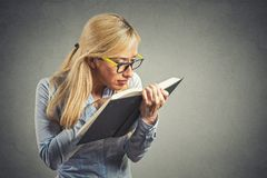 Woman with eye glasses trying read book, has bad vision Royalty Free Stock Image