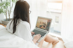 Woman with eye glasses Using Laptop In Bedroom by the window Royalty Free Stock Image