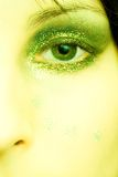 Woman eye make-up. Green eye, half face of a woman, glamorous make-up in shades of green and glitter, beautiful skin royalty free stock photography