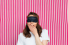 Woman with eye mask acting sleepy. Girl wearing black sleeping mask covering her open mouth with hand acting sleepy on striped background Stock Photography
