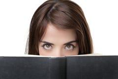 Woman eye peeking over book Stock Photos