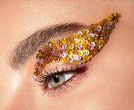 Woman eye with yellow sequins makeup closeup. Portrait Royalty Free Stock Images