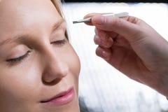 Woman during eyebrow depilation Stock Photos