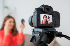 Woman with eyebrow pencil recording video at home Stock Photo