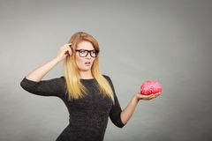 Woman in eyeglasses being confused holding brain Stock Photo