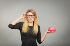 Woman in eyeglasses being confused holding brain Royalty Free Stock Photo