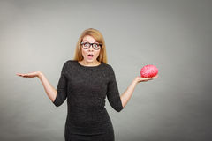 Woman in eyeglasses being confused holding brain Stock Photos