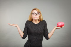 Woman in eyeglasses being confused holding brain Royalty Free Stock Images