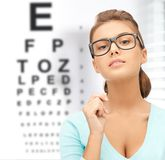 Woman in eyeglasses with eye chart. Medicine and vision concept - woman in eyeglasses with eye chart Royalty Free Stock Photography