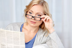 Woman in eyeglasses reading newspaper at home Royalty Free Stock Photos