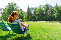 Woman in eyeglasses relax on greenfield. Stock Photo