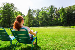 Woman in eyeglasses relax on greenfield. stock image