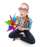 Woman in eyeglasses sitting on floor with windmill Royalty Free Stock Image