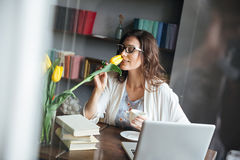 Woman in eyeglasses sitting at table with cup of tea. Portrait of a beautiful mature woman in eyeglasses sitting at the table with cup of tea and smells tulip stock photos