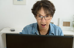 Woman with eyeglasses websurfing on laptop Stock Image