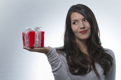 Woman eyeing a pretty red gift Royalty Free Stock Photography