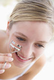 Woman with eyelash curler Stock Photography