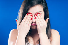 Woman with eyes closed. By hands on blue background Royalty Free Stock Images