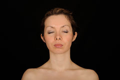 Woman with eyes closed. Portrait of young woman with eyes closed, black background royalty free stock images