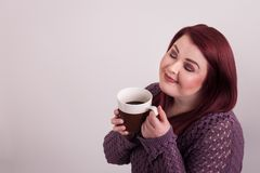 Woman eyes closed enjoying a cup of black coffee. Young woman eyes closed holding mug close to her enjoying a cup of warm black coffee royalty free stock photo