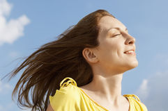 Woman With Eyes Closed Enjoying Sunlight Against Sky Royalty Free Stock Images