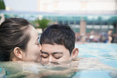 Woman with eyes closed kissing man on the cheek in the water in the pool Stock Image