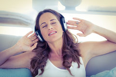 Woman with eyes closed listening to music on sofa Stock Image