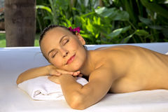 Woman with eyes closed, lying on a spa bed. Stock Photo