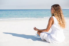 Woman with eyes closed meditating at beach during sunny day Stock Images