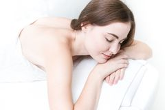 Woman eyes closed smile laying relax in spa. Beautiful woman eyes closed smile laying relax in spa white clean tone royalty free stock photos