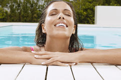 Woman With Eyes Closed Smiling At Poolside Stock Photos